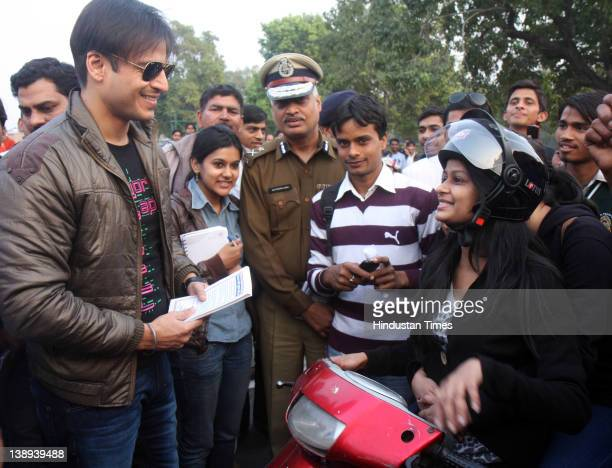 Bollywood actor Vivek Oberoi explains the need of wearing a helmet to young mopedriding girls near India Gate on February 13 2012 in New Delhi India...