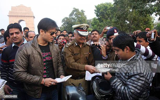 Bollywood actor Vivek Oberoi explains the need of wearing a helmet to a motor cyclist near India Gate on February 13 2012 in New Delhi India Oberoi...