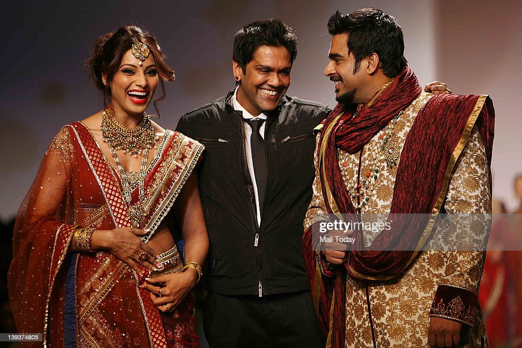 Bollywood actors Bipasha Basu left and Madhavan right walk the runway with designer Rocky S on Day 4 of the Wills Lifestyle India Fashion Week 2012...