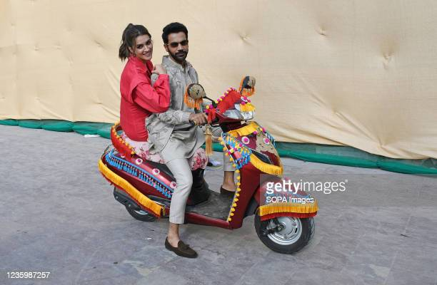Bollywood actors Rajkummar Rao and Kriti Sanon, poses for photos on a scooter for a promotional event of their upcoming film 'Hum Do Hamare Do' in...