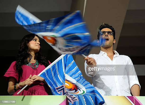 Bollywood actors Zayed Khan and Dia Mirza wave the Mumbai Indians team flags before the start of the Champions League Twenty20 cricket group B match...