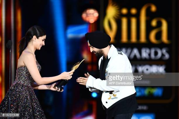 Bollywood actor/singer Diljit Dosanjh accepts Best Debut actor award from actress Alia Bhatt during the 18th International Indian Film Academy...