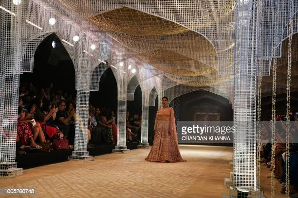 Bollywood actress Aditi Rao Hydari presents a creation by Indian designer Tarun Tahiliani during the India Couture Week 2018 in New Delhi on July 25...