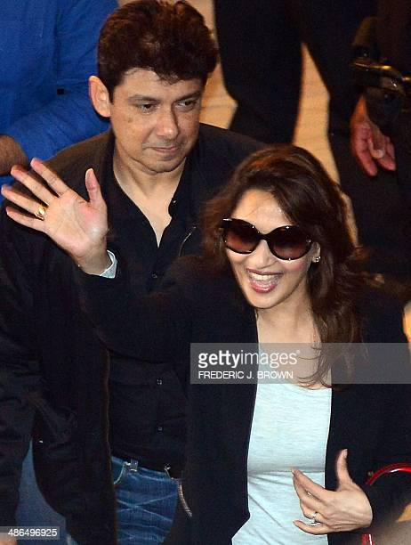 Bollywood actress Madhuri Dixit flanked by her husband Sriram Nene waves to fans as she arrives for a press conference at the Hilton Downtown Hotel...