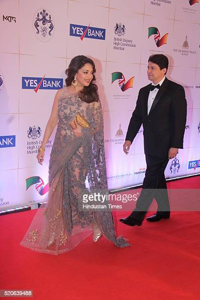 Bollywood actress Madhuri Dixit with her husband Shiram Nene arrives for the Bollywood theme dinner at the Taj Palace Hotel on April 10 2016 in...