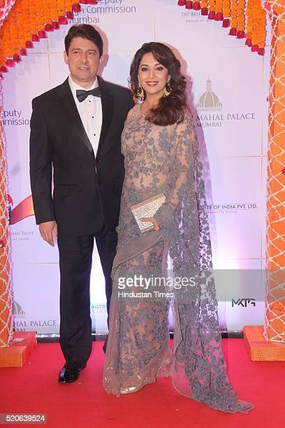 Bollywood actress Madhuri Dixit with her husband Shriram Nene poses for the cameras as they arrive for the Bollywood theme dinner at the Taj Palace...