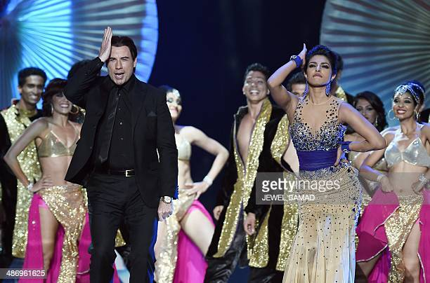 Bollywood actress Priyanka Chopra dances and Hollywood actor John Travolta dance on stage during the fourth and final day of the 15th International...