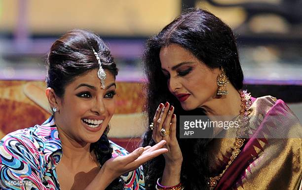 Bollywood actress Priyanka Chopra dances with veteran actress Rekha during the International Indian Film Academy awards ceremony in Singapore on June...
