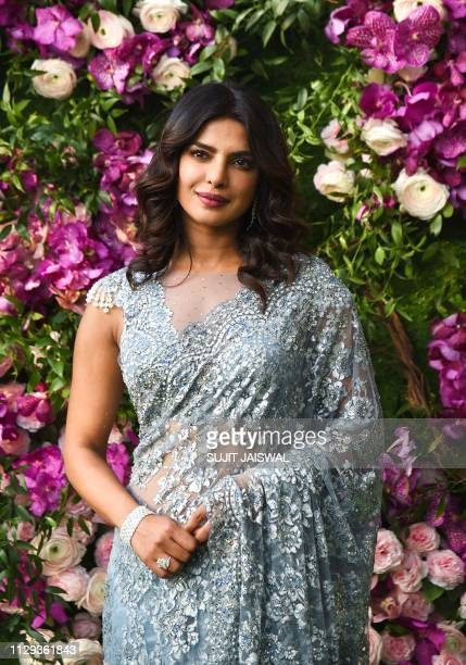 Bollywood actress Priyanka Chopra poses for photographs as she arrives to attend the wedding ceremony of Akash Ambani son of Indian businessman...
