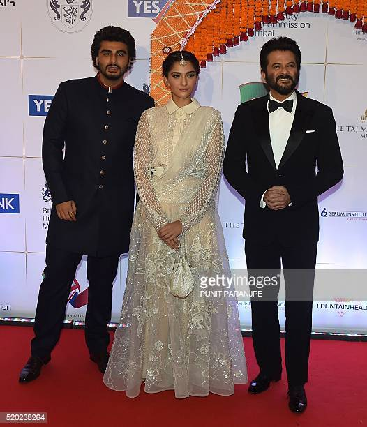 Bollywood actress Sonam Kapoor actors Anil Kapoor and Arjun Kapoor pose for photographers after arriving for the Charity Gala reception attended by...