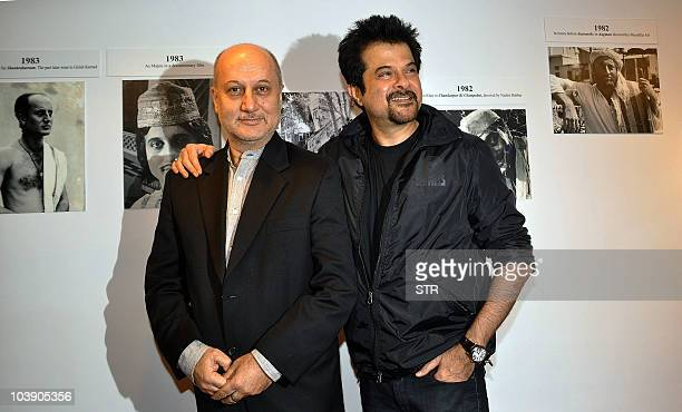 Bollywood film actors Anupam Kher and Anil Kapoor pose during the inauguration of artist Geeta Dass's exhibition of paintings based on Kher�s...