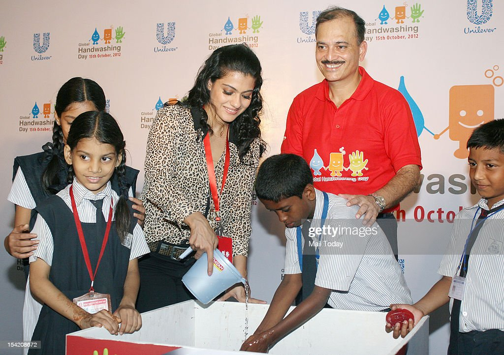Bollywood film actress Kajol and CEO and MD Hindustan Unilever Nitin Paranjpe assist children in washing their hands during the campaign to promote...