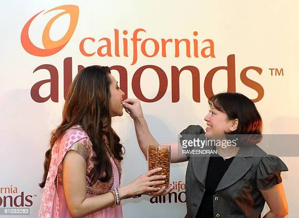Bollywood film actress Karisma Kapoor is fed a Californian almond by Almond Board of California AsiaPacific Associate Director Kristi Saitama during...