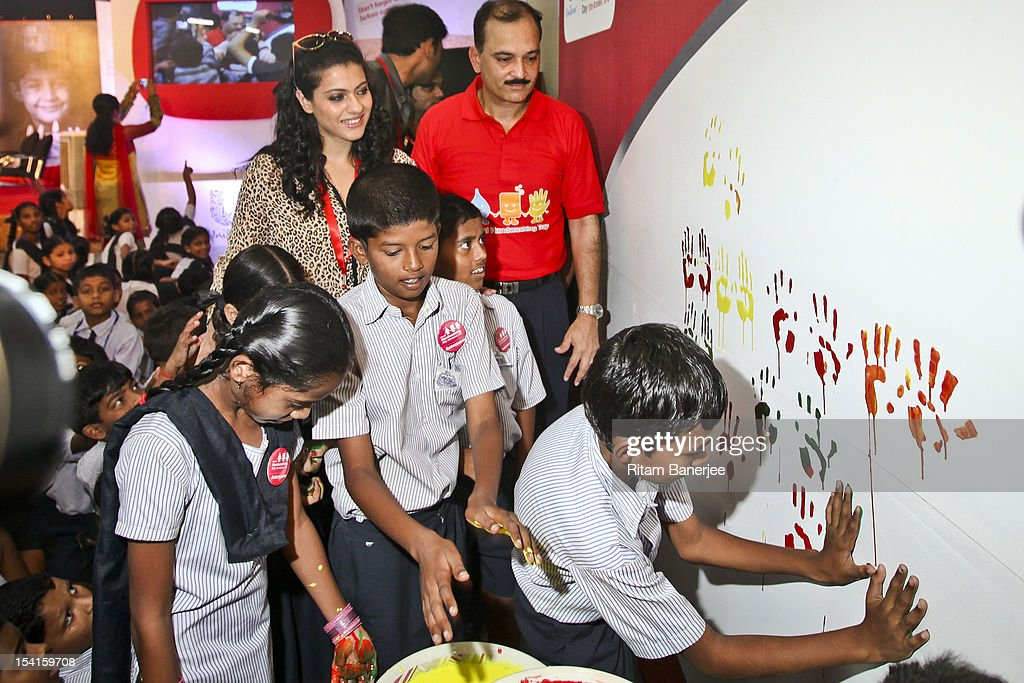 Bollywood movie actress Kajol and CEO MD of Unilever India Nitin Paranjpe look on as children place handprints on a board during a Global Handwash...