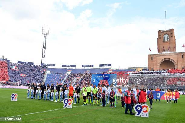 Bologna FC and SS Lazio players hold the logo celebrating the 90th annyversary of the Serie A during the Serie A match between Bologna FC and SS...
