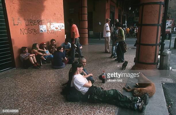 Bologna: Junge Leute sitzen auf dem Gehweg unter einer Galerie in Bologna- Mai 2000