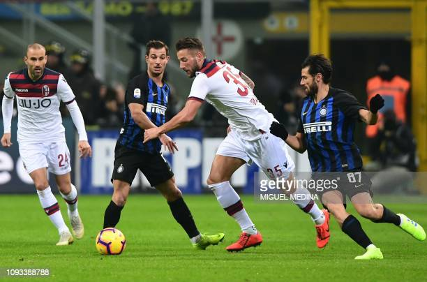 Bologna's Dutch defender Mitchell Dijks challenges Inter Milan's Portuguese defender Cedric Soares and Inter Milan's Italian midfielder Antonio...