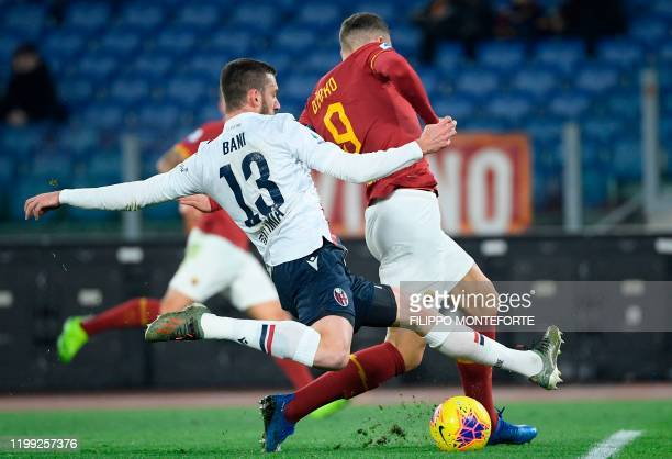 Bologna's Italian defender Mattia Bani is tackled by AS Roma's Bosnian forward Edin Dzeko during the Italian Serie A football match between AS Roma...