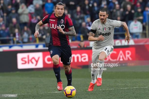 Bologna's Paraguayan forward Federico Santander outruns Juventus' Italian defender Leonardo Bonucci during the Italian Serie A football match Bologna...