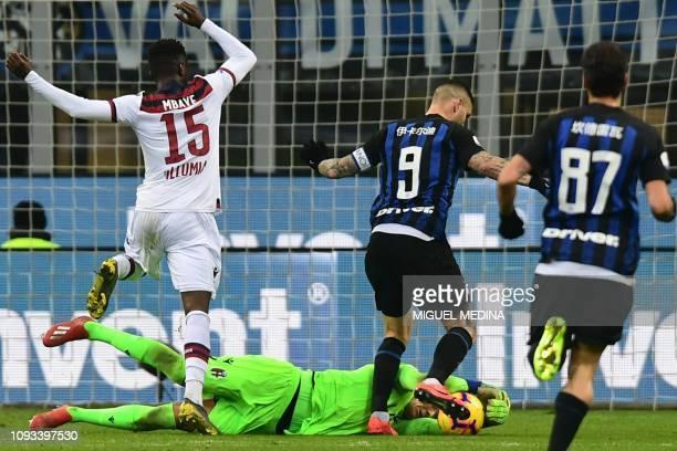 Bologna's Polish goalkeeper Lukasz Skorupski dives to grab the ball in the feet of Inter Milan's Argentine forward Mauro Icardi during the Italian...