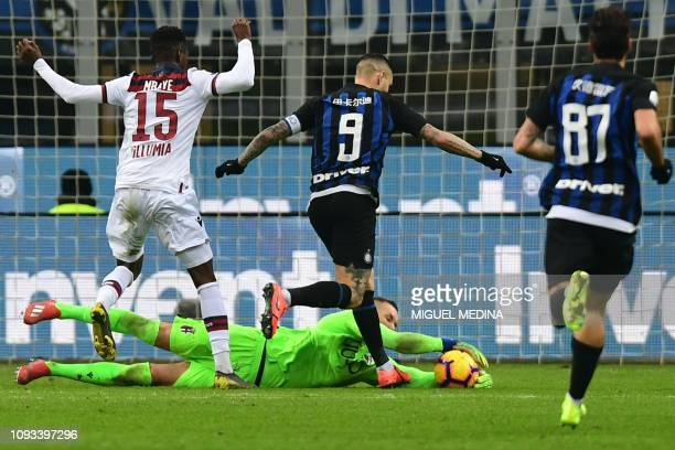 Bologna's Polish goalkeeper Lukasz Skorupski grabs the ball in the feet of Inter Milan's Argentine forward Mauro Icardi during the Italian Serie A...