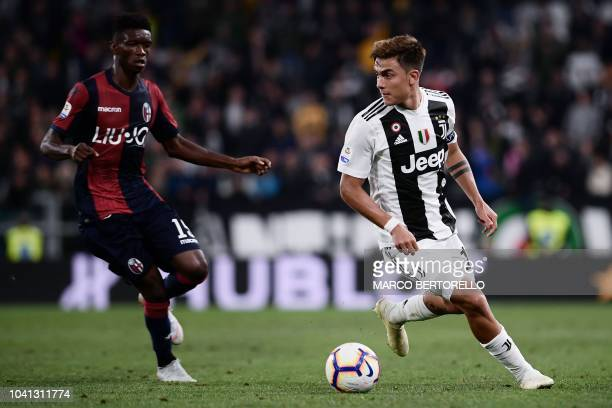 Bologna's Senegalese defender Ibrahima Mbaye fights for the ball with Juventus' Argentinian forward Paulo Dybala during the Italian Serie A football...