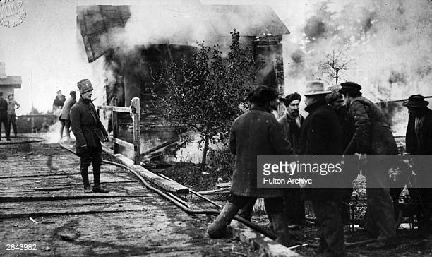 Bolsheviks confer as firemen try to control a burning building in the background during the Russian Revolution