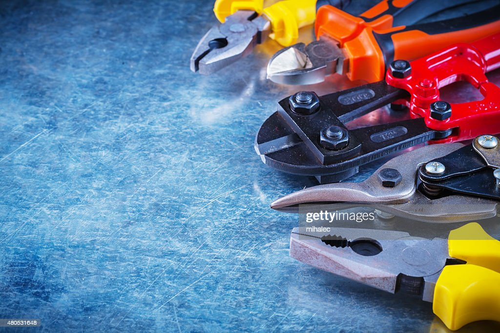 Bolt cutter tin snips cutting pliers gripping tongs on scratched : Stock Photo