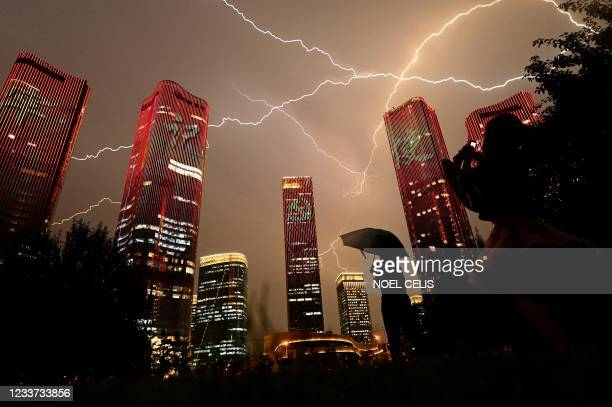 Bolt of lightning crosses the sky as people look at buildings displaying a light show on the eve of the 100th anniversary of the Chinese Communist...