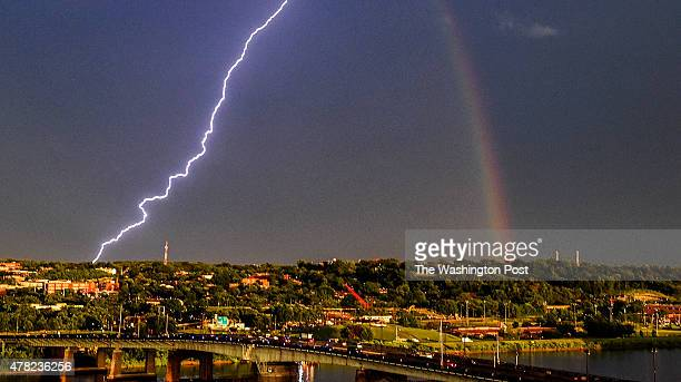 Bolt of lightning strikes across the Anacostia river as a rainbow graces the sky near Nationals Park as the Washington Nationals and Atlanta Braves...