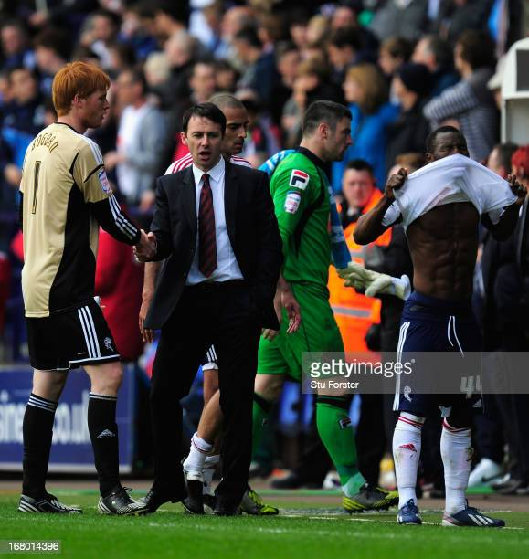 Bolton manager Dougie Freedman shakes hands with keeper Adam Bogdan as Medo Kamara reacts the npower Championship match between Bolton Wanderers and...