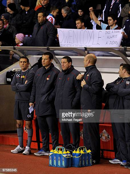 Bolton manager Owen Coyle stands in front of Burnley fans holding a banner regarding his decision to leave their club earlier in the season before...
