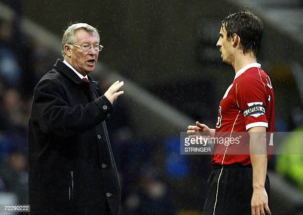 Manchester United football club manager Alex Ferguson speaks with captain Gary Neville during their English Premiership football match against Bolton...