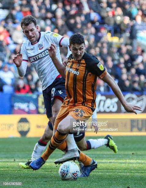 Bolton Wanderers' Christian Doidge competing with Hull City's Tommy Elphick at Macron Stadium on October 27 2018 in Bolton England