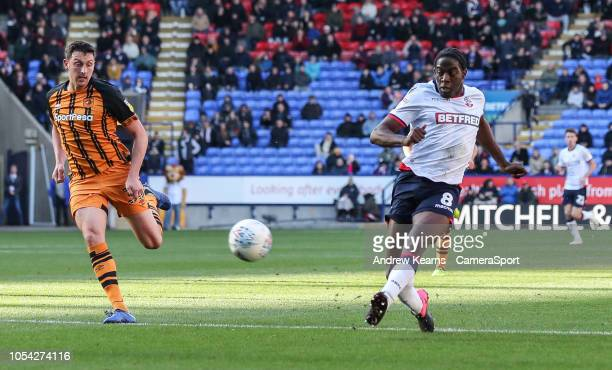 Bolton Wanderers' Clayton Donaldson shoots under pressure from Hull City's Tommy Elphick at Macron Stadium on October 27 2018 in Bolton England