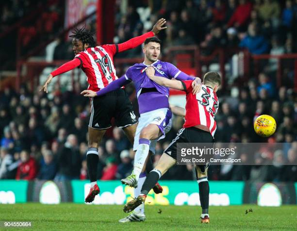 Bolton Wanderers' Gary Madine battles with Brentford's Romaine Sawyers and Chris Mepham during the Sky Bet Championship match between Brentford and...