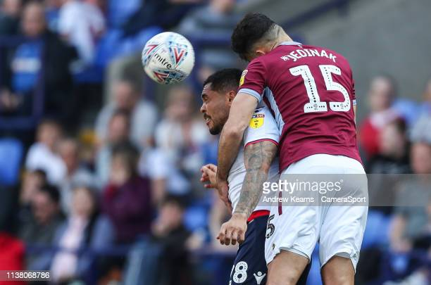 Bolton Wanderers' Josh Magennis competing with Aston Villa's Mile Jedinak during the Sky Bet Championship match between Bolton Wanderers and Aston...
