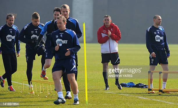 Bolton Wanderers manager Owen Coyle looks on as Bolton Wanderers' Bulgarian midfielder Martin Petrov and other teammates attend a training session at...