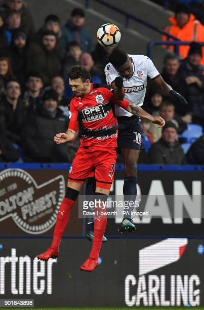 Bolton Wanderers' Sammy Ameobi out jumps Huddersfield Town's Scott Malone during the FA Cup third round match at the Macron Stadium Bolton