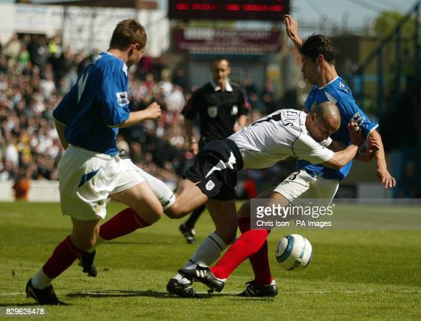 Bolton Wanderers' Stelios Giannakopolous is challenged by Portsmouth's Matt Taylor and Dejan Stefanovic .