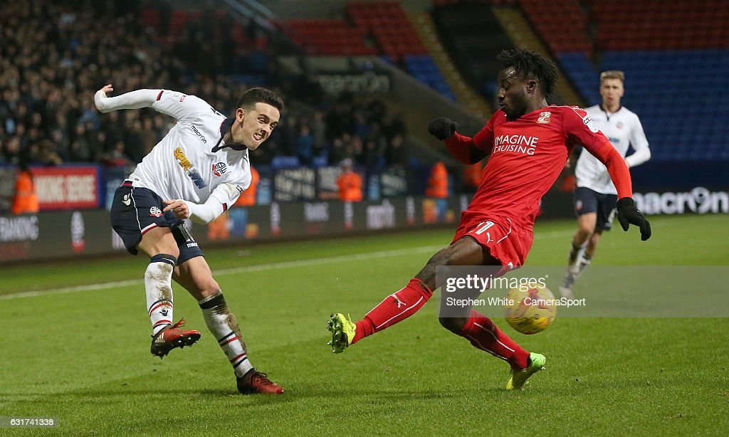 Bolton Wanderers' Zach Clough crosses the ball despite the attentions of Swindon Town's Sheik Mohamed Fankaty Dabo during the Sky Bet League One match between Bolton Wanderers and Swindon Town at Macron Stadium on January 14, 2017 in Bolton, England.