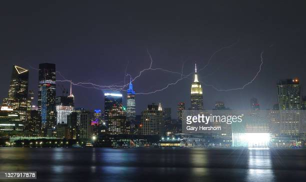 Bolts of lightning streak across the sky behind the Empire State Building and One Vanderbilt in New York City during a thunderstorm on July 9, 2021...