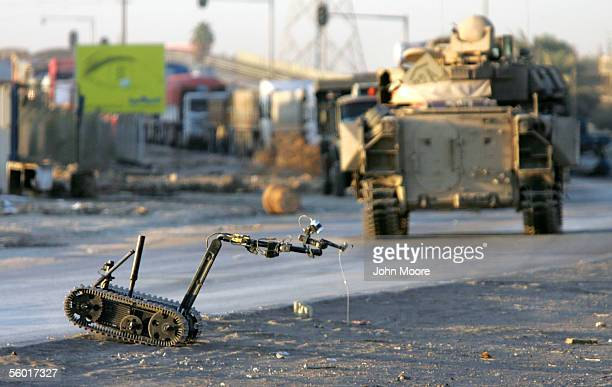 A bomb diffusing robot operated by remote control by an Army bomb squad carries back the blasting cap of a roadside bomb also known as an improvised...