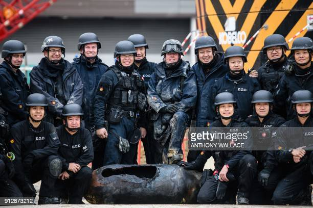 Bomb disposal expert Adam Roberts and colleagues from the explosive ordinance disposal police unit pose with a defused USmade bomb dropped during...
