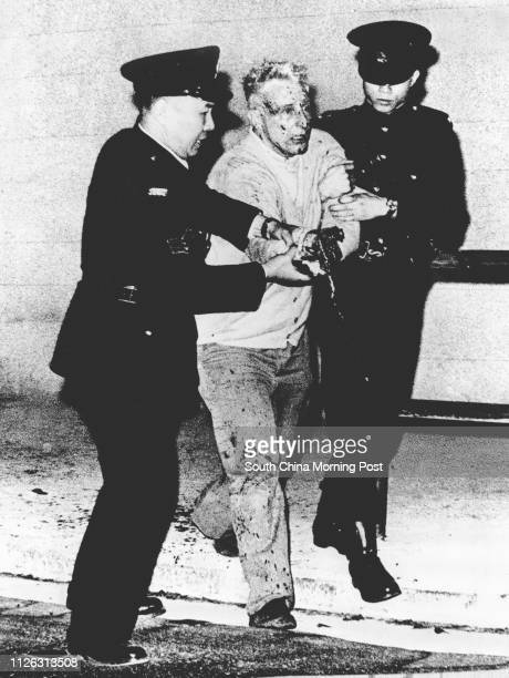 Bomb disposal expert Norman Hill accompanied by police after his right hand was blown off during an examination of a suspect package outside Central...