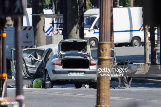 TOPSHOT A bomb disposal police officer checks a car in a sealed off area on the ChampsElysees avenue in Paris on June 19 2017 after a car crashed...