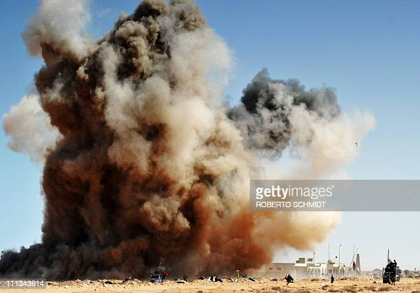 A bomb dropped by a Kadhafi loyalist Airforce fighter jet explodes as Libyan rebel fighters run for cover on March 11 2011 some 10 kilometers east of...