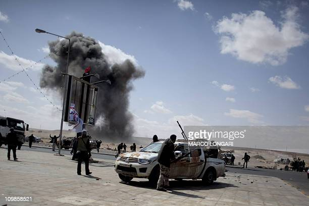 A bomb dropped by an airforce jet explodes next to Libyan rebel fighters gathering on the outskirts of the oilrich town of Ras Lanuf on March 8 2011...
