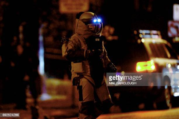 TOPSHOT A bomb squad member exits a residential building in the Melbourne bayside suburb of Brighton on June 5 after a woman was held against her...
