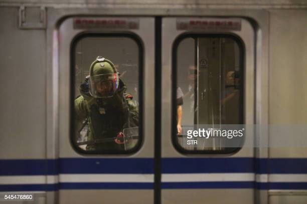 TOPSHOT A bomb squad officer in protective gear is seen entering the inside of a train carriage that was involved in a blast in Taipei on July 8 2016...